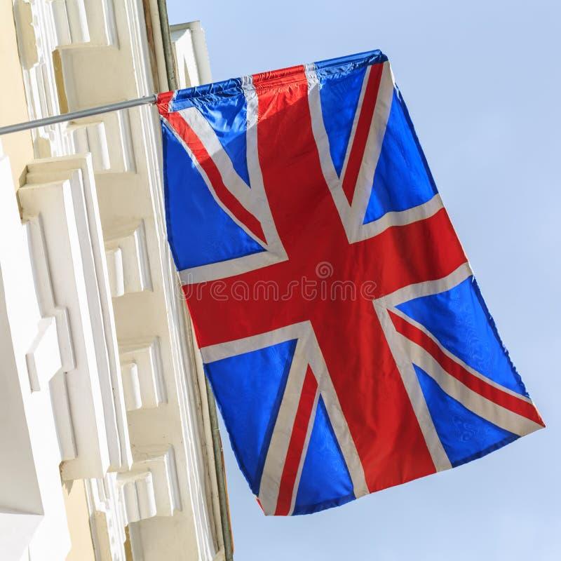 La bandiera di Britannici vola sulla costruzione dell'hotel nella città turistica immagini stock