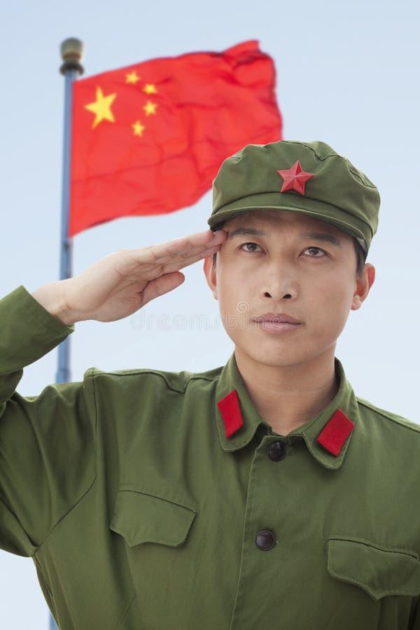 La bandiera di Saluting China serio del soldato immagine stock libera da diritti