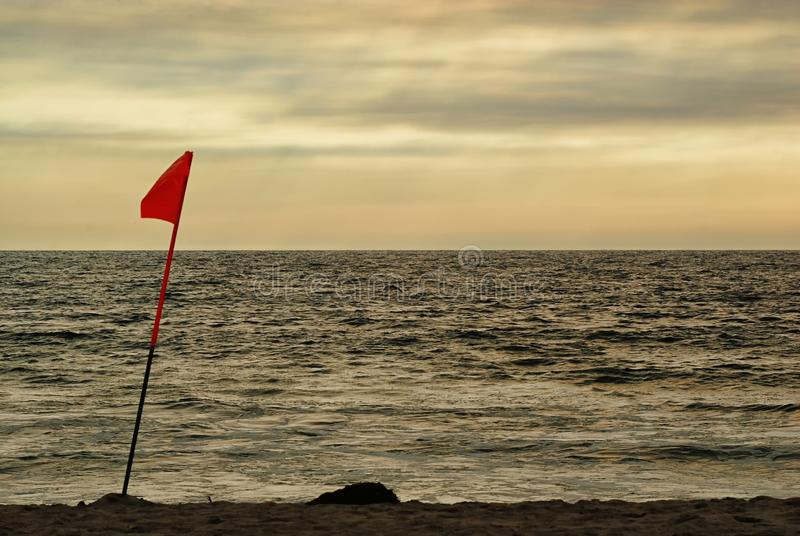 La bandiera di un bagnino alla luce di pomeriggio di una spiaggia nuvolosa fotografie stock libere da diritti