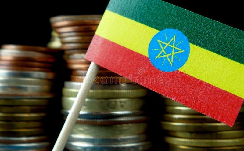 La bandiera etiopica che ondeggia con la pila di soldi conia immagine stock