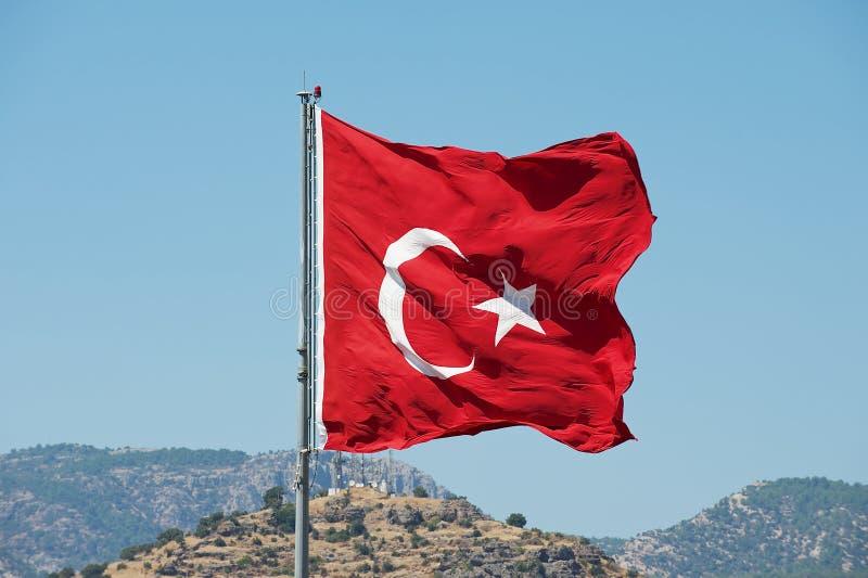 La bandiera nazionale turca all'asta della bandiera ondeggia sopra una collina con un cielo blu dell'estate ai precedenti in Bodr fotografia stock libera da diritti