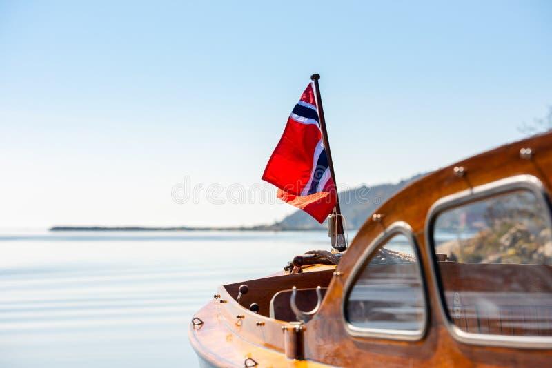 La bandiera norvegese nell'albero poppiero di una barca di legno fotografia stock