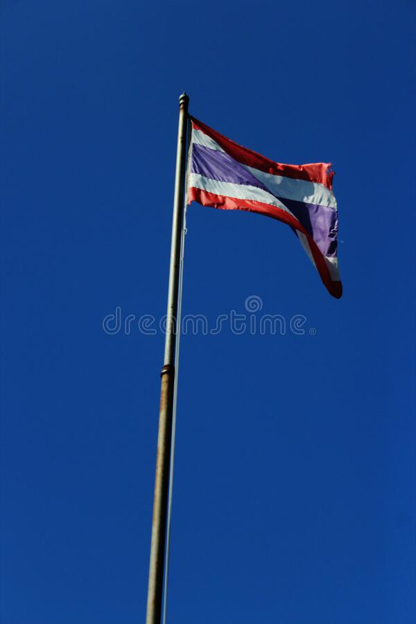 La bandiera thailandese sventola con un'asta alta con sfondo azzurro foto fotografia stock libera da diritti