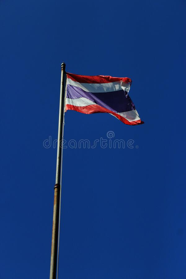 La bandiera thailandese sventola con un'asta alta con sfondo azzurro foto fotografie stock