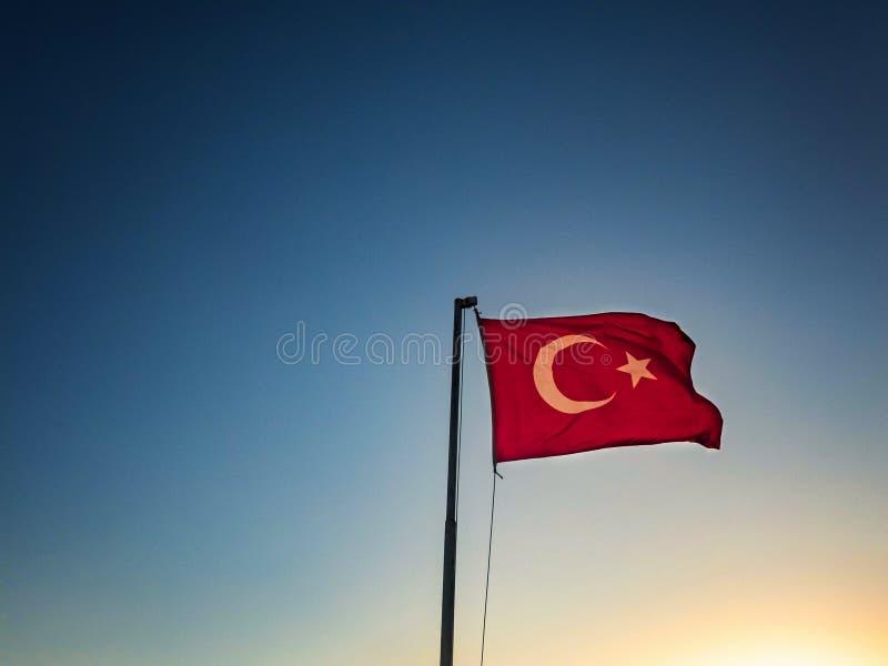 La bandiera turca sta ondeggiando contro il cielo ai precedenti fotografie stock libere da diritti