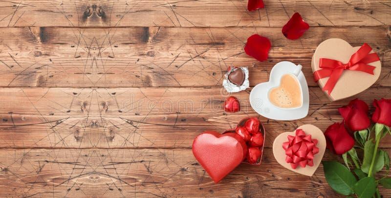 La bannière de Saint-Valentin avec la tasse de café, chocolat de forme de coeur, s'est levée des fleurs et des boîte-cadeau sur l photos libres de droits