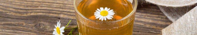 La bannière de la tasse de thé avec la camomille fleurit sur le fond en bois rustique photo stock