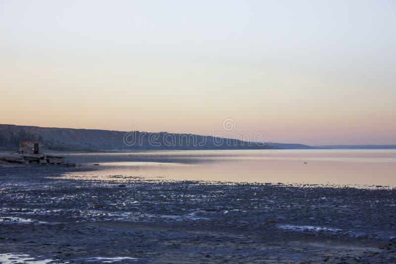 La banque foncée de séchage de l'estuaire dans les couleurs du soleil de dépassement d'été La soirée obscurcit photo stock