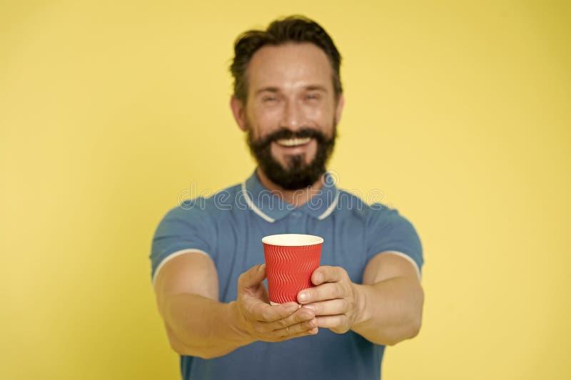 La barba y el bigote del individuo sostiene la taza de papel de t? o de caf? Bebida de la oferta a usted Cuidado experimentado de imagen de archivo