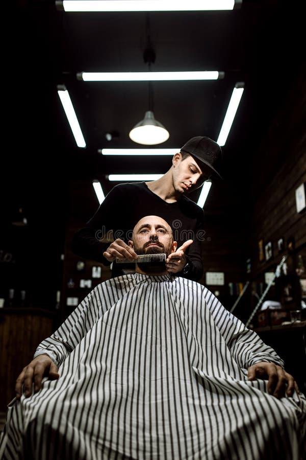 La barbería elegante El peluquero de la moda ordena la barba del hombre brutal que se sienta en la butaca fotos de archivo