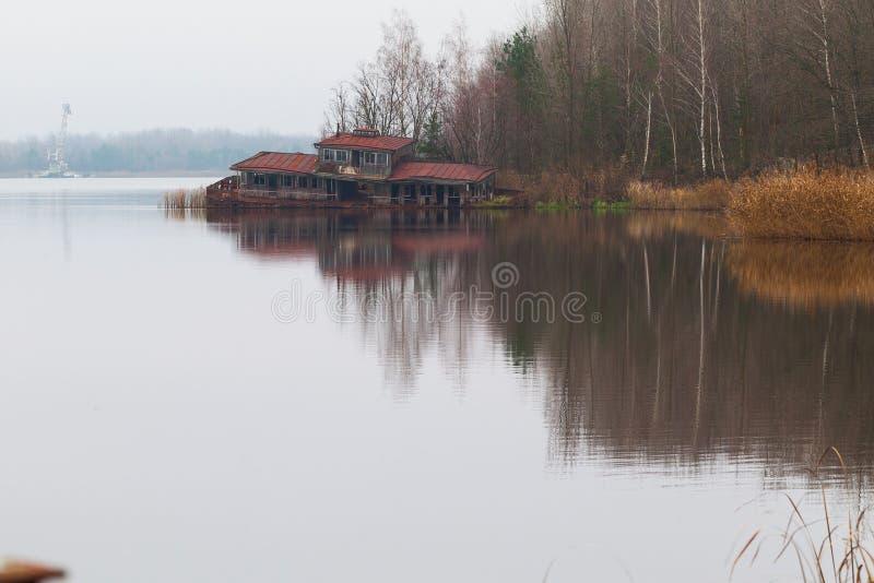 La barca d'affondamento dispone la costruzione su uno stagno di Yanov nella città di Pripyat, la zona di esclusione di Cernobyl,  fotografia stock