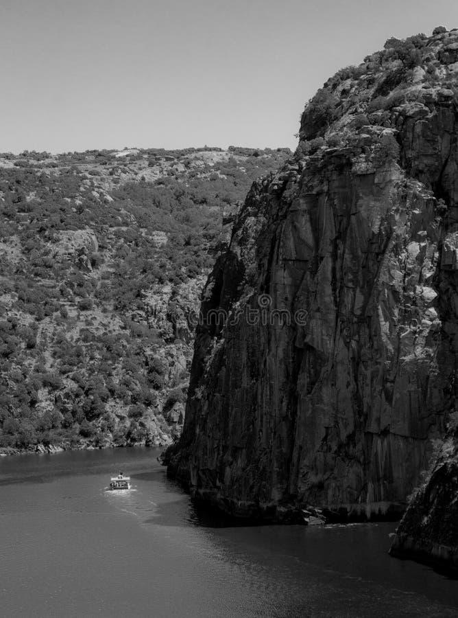La barca di crociera passa vicino alla scogliera enorme fotografia stock