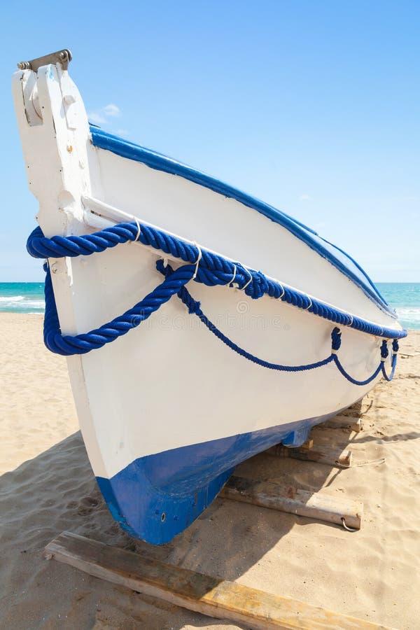 La barca di legno bianca mette sulla spiaggia sabbiosa, Spagna immagine stock libera da diritti