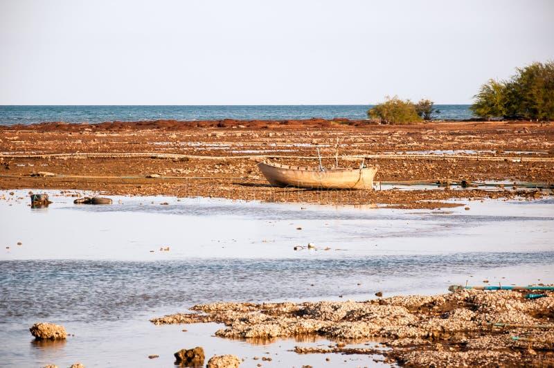 La barca di legno gialla e vecchia nella marea di neap con i peri leggeri caldi immagini stock libere da diritti