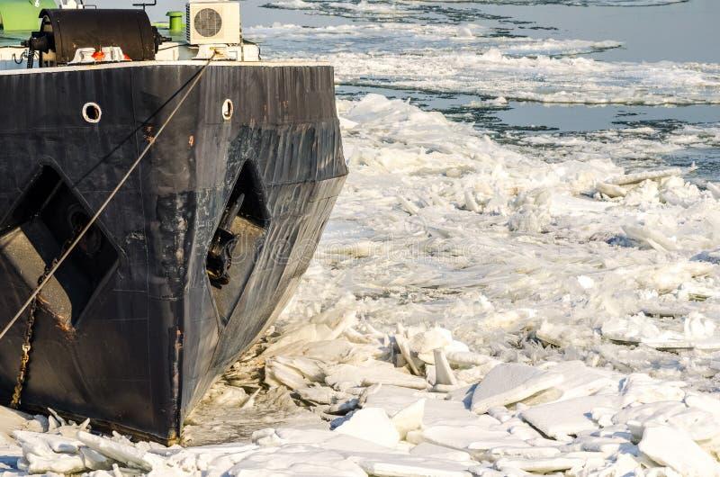La barca ha attaccato in ghiaccio dell'acqua di fiume congelata nella temperatura del freddo dell'inverno fotografie stock libere da diritti
