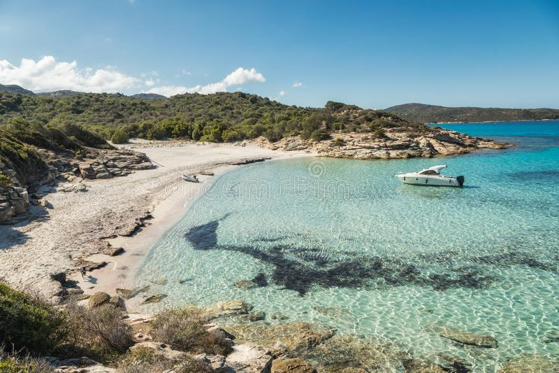 La barca ha attraccato in una piccola baia con la spiaggia sabbiosa in Corsica immagini stock