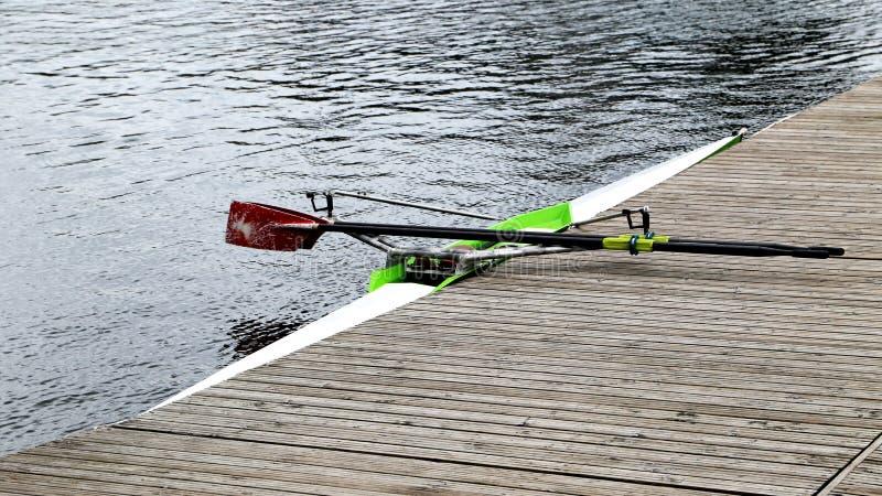 La barca lunga di sport con i remi si leva in piedi al pilastro di legno al giorno pieno di sole immagini stock