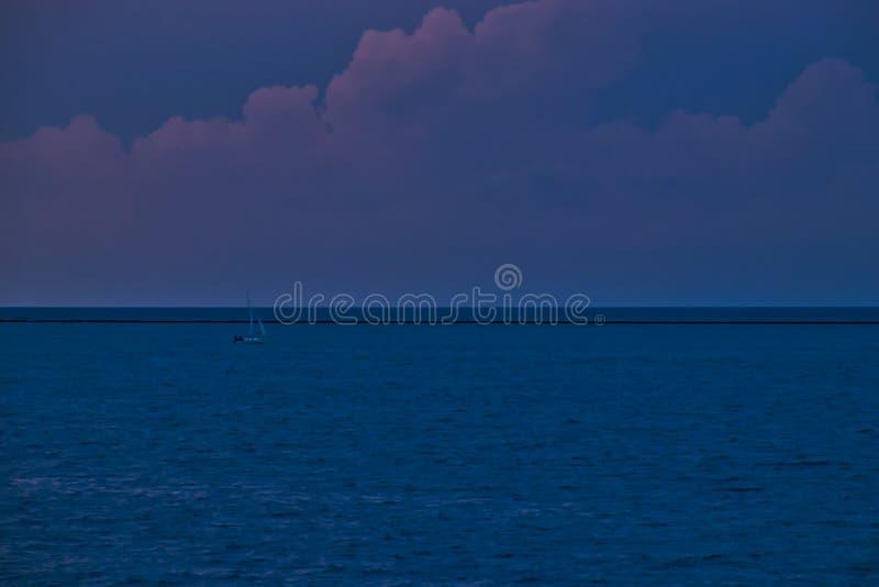 La barca sola attraversa il lago Michigan durante il tramonto porpora in Chicago immagini stock