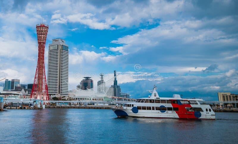 La barca sta passando la torre del porto di Kobe immagine stock