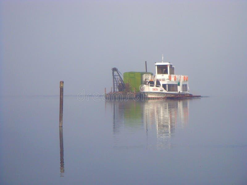 La barca sul d'alto mare dalla nebbia gradisce un ona del fantasma un lago fotografia stock