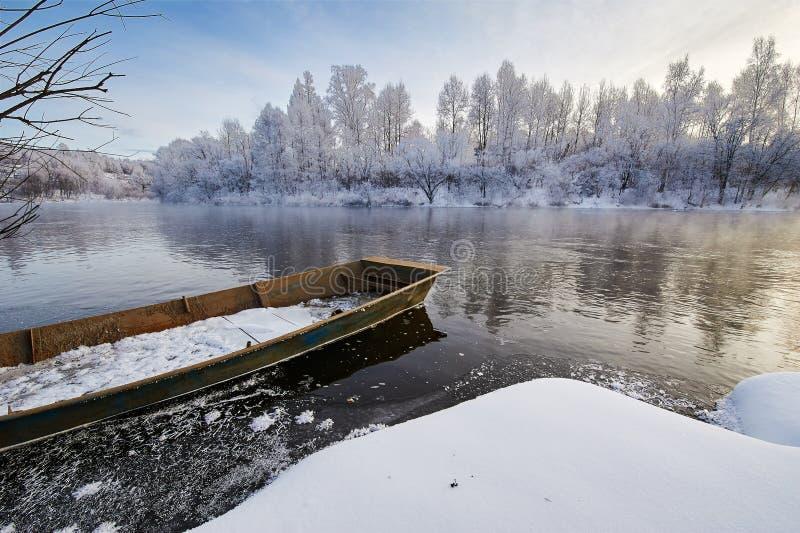 La barca sul fiume di inverno immagini stock