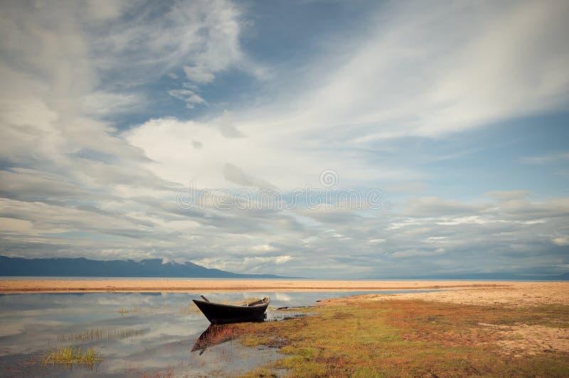 La barca sul lago sotto cielo blu fotografie stock libere da diritti