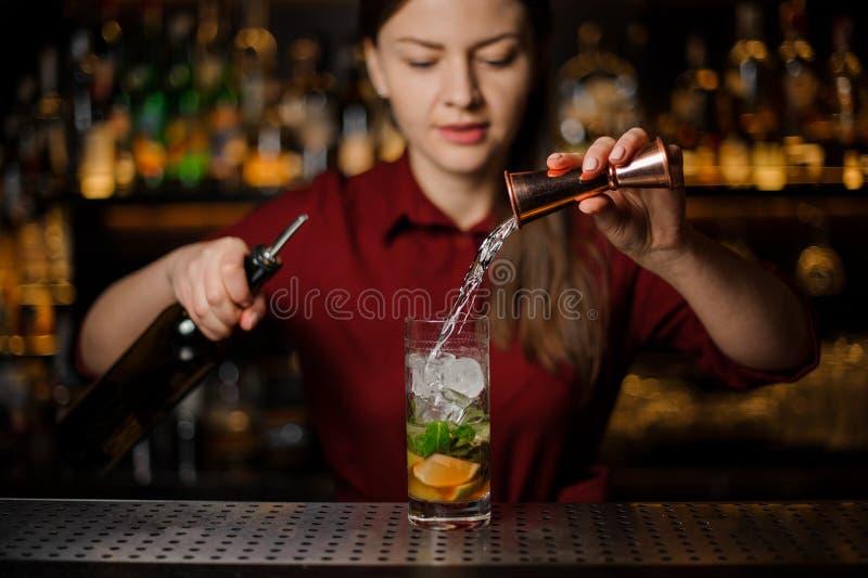 La barmaid accomplit la préparation du mojito, ajoutant un blanc photos stock