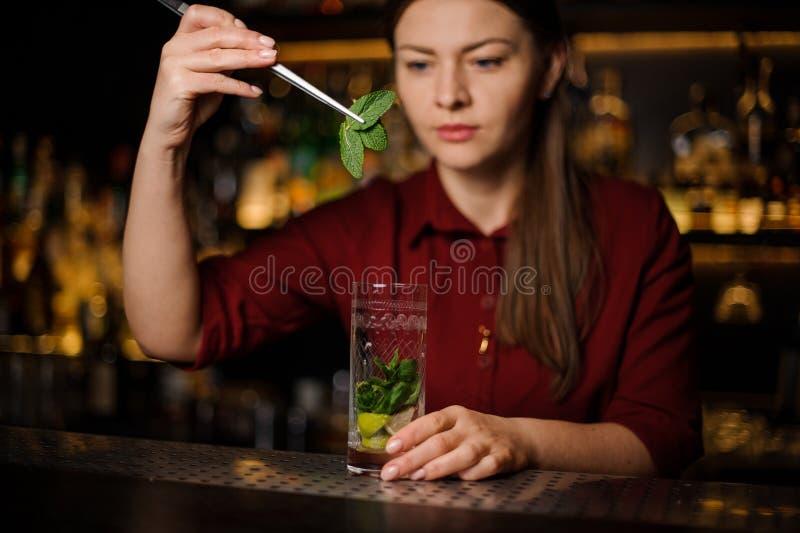 La barmaid blonde dans une robe rouge prépare un mojito ajoutant des feuilles de photo stock