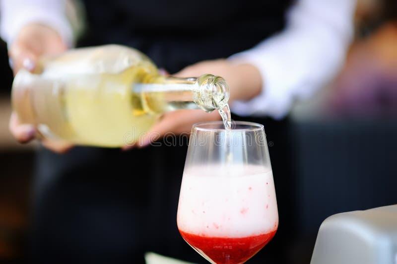 La barmaid de femme verse l'apéritif dans le verre image stock