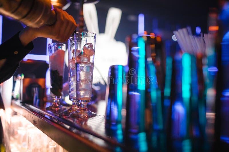 La barmaid de fille prépare un cocktail dans la boîte de nuit photo stock