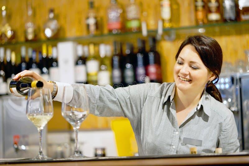 La barmaid de fille verse le vin dans un verre de vin photo libre de droits