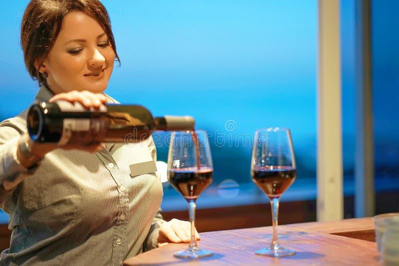 La barmaid de fille verse le vin dans un verre de vin photo stock