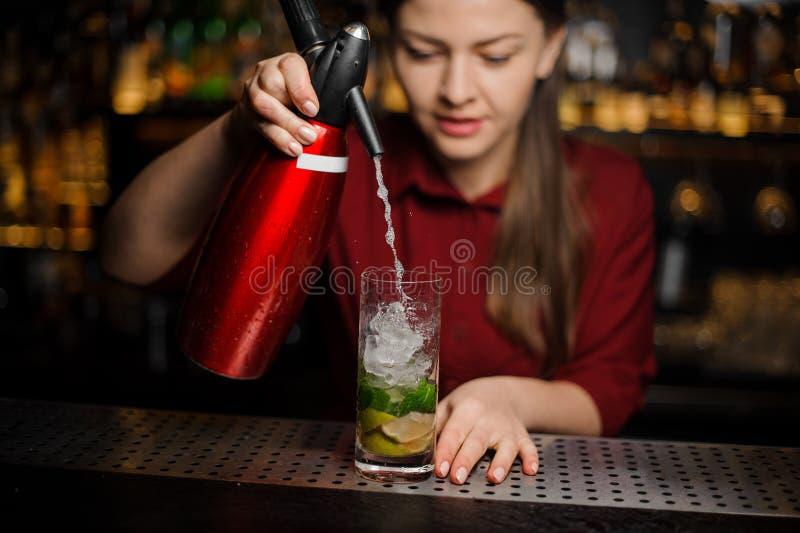 La barmaid finit de préparer un cocktail alcoolique de mojito, ajoutant s photo stock