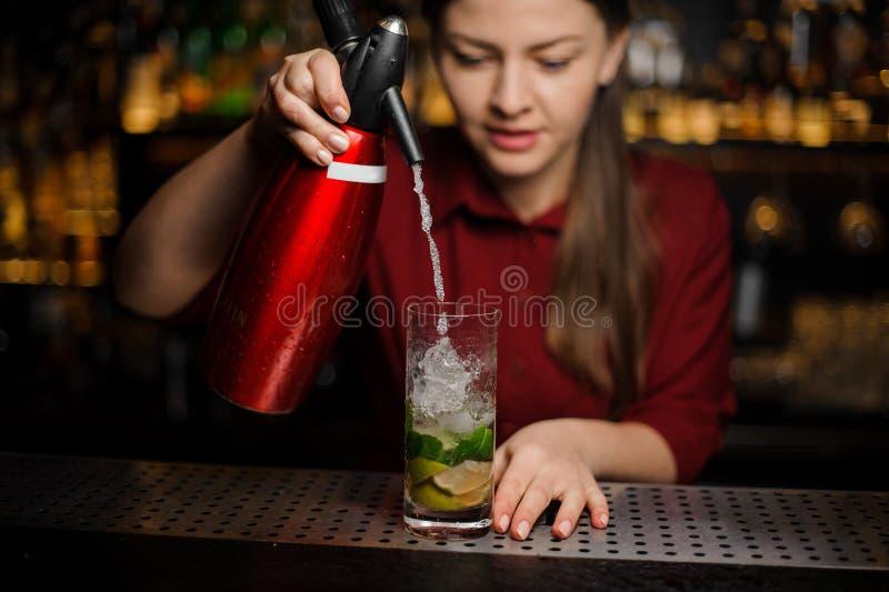 La barmaid finit de préparer un mojito, ajoutant l'eau de seltz au Cr photographie stock libre de droits
