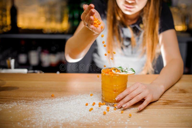 La barmaid finit la préparation du cocktail alcoolique en ajoutant un amer de l'argousier photo libre de droits