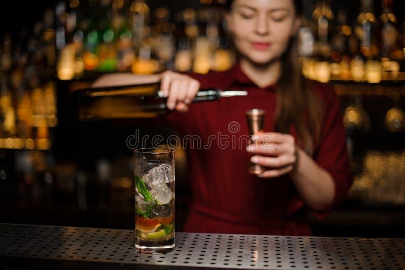 La barmaid mignonne prépare un mojito dans un verre cristal, ajoutant r foncé photographie stock