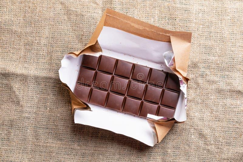 La barra de chocolate entera en envoltura de papel abierta está mintiendo en la arpillera imagen de archivo