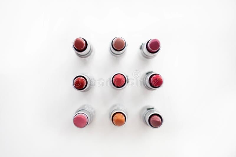 La barra de labios en diversos colores naturales arregló en un cuadrado en un fondo blanco Visi?n superior imagen de archivo libre de regalías