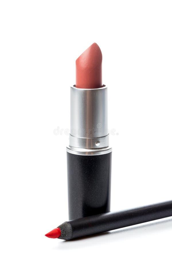 La barra de labios y compone el lápiz aislado en blanco fotografía de archivo