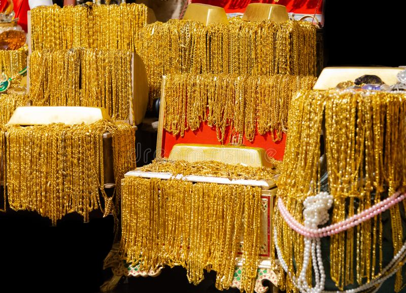 La barra de oro y el collar del oro muchos cuelgan en la foto negra del fondo de la textura de la bandeja del terciopelo fotos de archivo