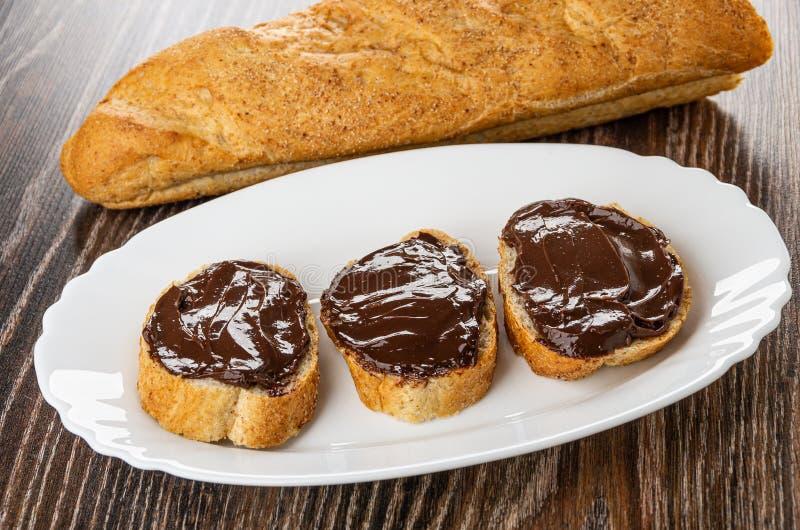 La barra de pan, bocadillos con el chocolate derritió el queso en plato en la tabla foto de archivo
