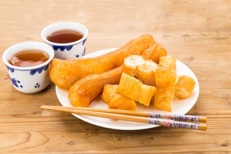 La barra de pan frito o usted Tiao sirvió con té chino en la tabla de madera fotografía de archivo