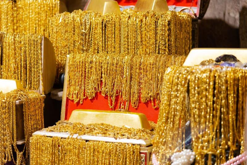La barra di oro e la collana dell'oro molti appendono sulla foto nera del fondo di struttura del vassoio del velluto fotografia stock