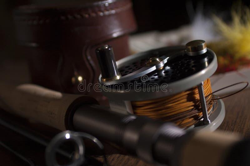 La barra y el carrete de pesca con mosca con el caso y la pluma de cuero vuela foto de archivo libre de regalías