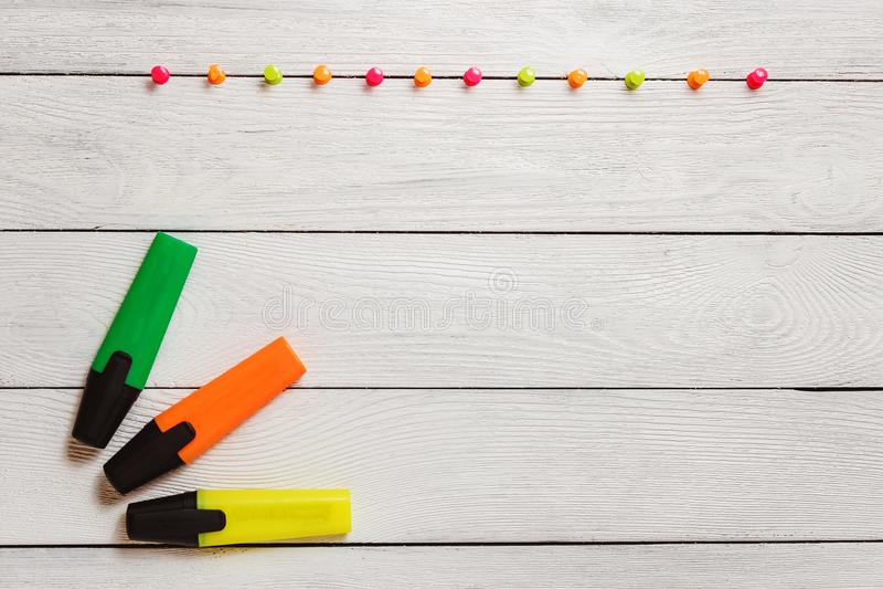 La barre de mise en valeur jaune, verte, orange, punaises colorées sur le Tableau en bois blanc, stationnaire, copient l'espace é photo stock