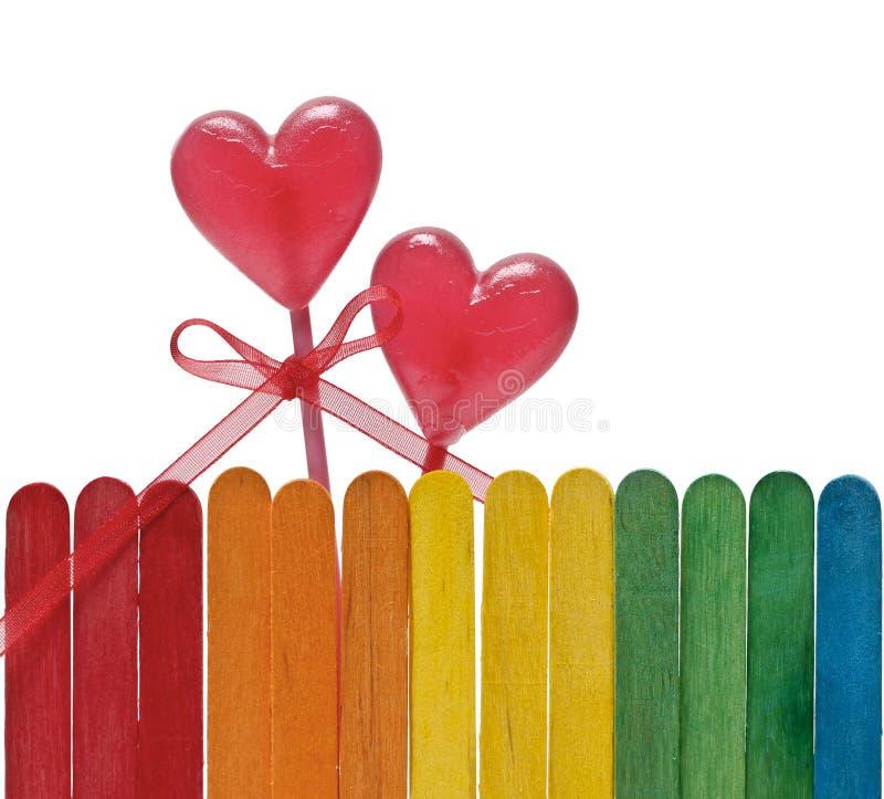 La barrière en bois dans des couleurs d'arc-en-ciel et deux lucettes au coeur forment photographie stock