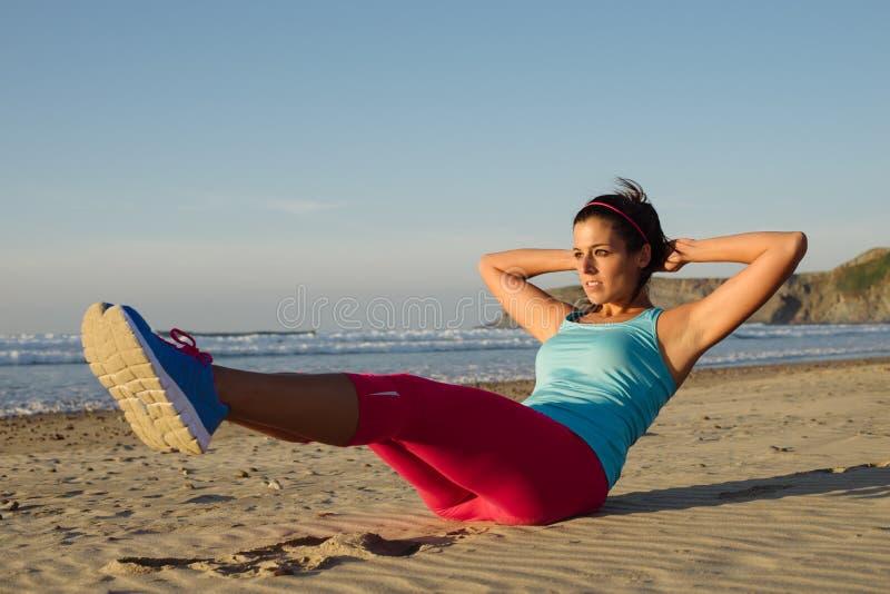 La base del entrenamiento de la mujer de la aptitud con la rodilla aumenta ejercicio foto de archivo libre de regalías