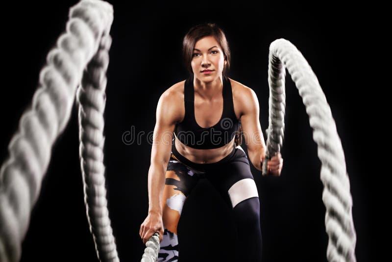 La batalla ropes la sesión Los jóvenes atractivos cupieron y entonaron a la deportista que se resolvía en el gimnasio funcional d foto de archivo libre de regalías