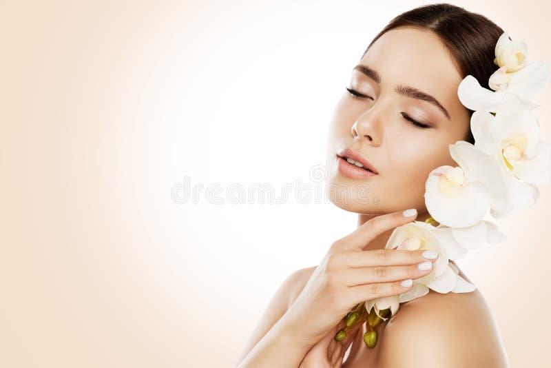 La beauté de femme, soins de la peau de visage composent, fleur d'orchidée dans les cheveux photographie stock