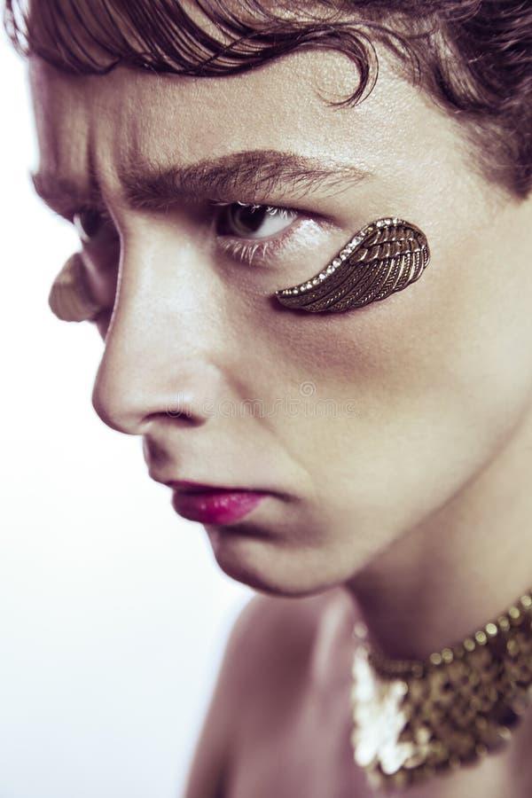 La beauté de haute couture du jeune modèle avec de l'or s'envole les bijoux piercing et le maquillage photo libre de droits